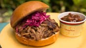 Pulled pork on a bun with red cabbage near a cup of chili
