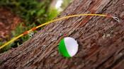 Close-up de uma vara de pesca com flutuador apoiada no tronco de uma árvore