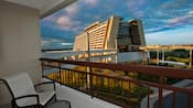 A Resort hotel balcony with a chair and table overlooking a walkway to Disney's Contemporary Resort
