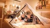 Deux enfants portant des chapeaux de fantaisie inspirés de l'Ouest lisent une carte avec une lampe de poche et une petite lanterne sous un tipi improvisé sur leur lit de chambre d'hôtel tandis que les adultes sont rassemblés autour de la table à manger