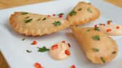 3 empanadas garnished with parsley, bell pepper and aioli