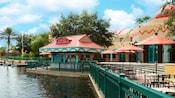 Un área con mesas cerca de un puerto, árboles, un hotel y un bar con un cartel que dice Laguna Bar