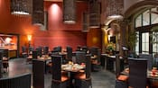A restaurant seating area with set tables, chairs and lighting fixtures