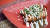 3 taquitos topped with queso, cream cheese, salsa and cilantro