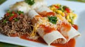 2 enchiladas topped with cheese, salsa and parsley near corn salsa, rice and beans and a burrito