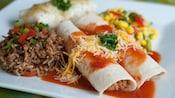 2 enchiladas cubiertas con queso, salsa y perejil, junto a salsa de maíz, arroz y frijoles, y un burrito