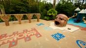 Un terrain de jeux d'inspiration maya est entouré de végétation et est composé de balançoires, d'un jeu modulaire et d'un bac à sable avec une grande statue vide en forme de tête maya.