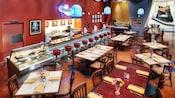Un petit restaurant classique avec un bar, des tables, des chaises et une affiche sur le mur sur laquelle on peut lire «The Fountain»