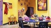 Sala de juegos para niños con mesa de artesanías, juguetes y un televisor de pantalla grande