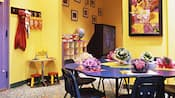 Une salle de jeux pour enfants avec une table de bricolage, des jouets et un téléviseur grand écran