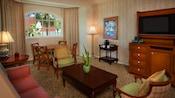 Una mesa baja con 2sillones cerca de una mesa de comedor con 4sillas, n sofá y un vestidor con TV