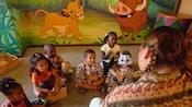 """Niños pequeños escuchan a un Miembro del Elenco narrar una historia en el Centro de actividades para niños """"Simba's Cubhouse"""""""