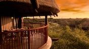 Un balcón con una mesa y sillas bajo un techo de paja, con vista a la sabana del Hotel al atardecer