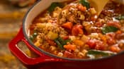 A wooden spoon stirs minestrone soup in a pot