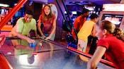 2 adolescentes jugando una partida de hockey de mesa en una galería de un Hotel de Disney