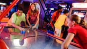 2 teens playing a game of air hockey against each other in a Disney hotel arcade