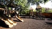 A gravel playground with slides and platforms under thatched roofs at Disney's Animal Kingdom Villas – Kidani Village