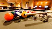 Close-up of a tan pool table with balls racked up next to a pool stick and chalk