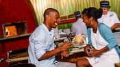 A couple laughs as they drink near food and a kitchen staff member