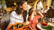 Una mujer y una niña sostienen binoculares sentadas en la mesa de un restaurante con platos de comida