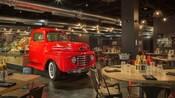 Restaurante bajo techo muestra un camión vintage con canastas de comida, mesas con bebidas, utensilios y sillas