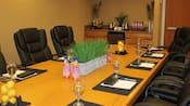 A boardroom with chairs, a set table and a bar including a mini fridge, tea, juice and fruit
