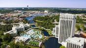 Un hôtel avec des bâtiments, un lac, une piscine, des arbres, une marina et une montgolfière