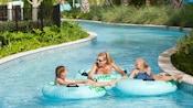 2enfants et une femme flottent dans une étendue d'eau sur des bouées sur lesquelles est écrit Float Lagoon