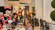 Dingo, Minnie Mouse et Pluto interagissent avec des enfants dans un restaurant