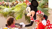 Minnie Mouse interacts with a young boy and a young girl