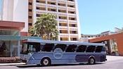 """Hotel con árboles cerca de un autobús con un letrero que dice """"Disney Springs Resort Area Hotels"""""""