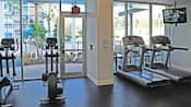 A fitness area with treadmills, a TV and elliptical machines