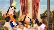 Goofy and Pluto interact with a family in a restaurant