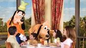 Dingo et Pluto interagissent avec une famille dans un restaurant