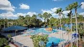 La piscine d'un hôtel avec des arbres, des chaises longues et une fontaine