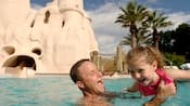 A father gleefully playing with his daughter in the Sandcastle Pool at Disney's Old Key West Resort
