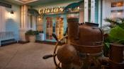 Un gouvernail de navire rétro et une colonne de direction en métal devant le restaurant Olivia'sCafé