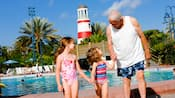 Grandfather with his two granddaughters by a pool at Disney's Old Key West Resort
