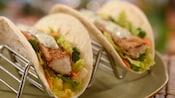 2 tacos de pescado con lechuga, pimientos, zanahorias y salsa tártara