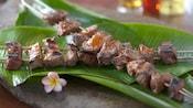 2kebabs de carne bovina perto de uma flor
