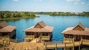 Three overwater bungalows are connected by a tiki walkways while Cinderella's Castle stands in the distance