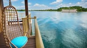 A hanging wicker chair on the terrace of an overwater bungalow looks out to the water and Resort