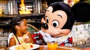 A small girl smiles with delight as a Hawaiian clad Mickey Mouse joins her for breakfast