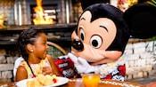 Uma garotinha sorri enquanto o Mickey Mouse havaiano se junta para o café da manhã
