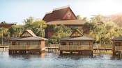 Small Polynesian themed houses built on a lagoon, with hotels of the same design in the background