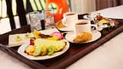Sliced pineapple, dragon fruit, papaya, kiwi, guava, lychee and kumquats near 2 cups of coffee, 2 croissants, a bowl of sugar, a container of milk, 2 glasses of ice and a pitcher of juice on a tray