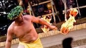 Un bailarín de fuego con un bastón en llamas