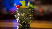 A drink in a mug fashioned to resemble a smiling shrunken head