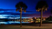 Vue nocturne du Disney'sPolynesianResort à partir d'une plage voisine