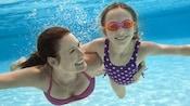 Uma mãe sorridente abraçada sua filha enquanto nadam embaixo d'água em uma piscina